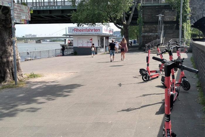 """Mittlerweile wohl verboten, aber bis Mitte Juni noch üblich: E-Scooter in Rheinnähe geparkt, an der Hohenzollernbrücke in Köln, bereitgestellt für den abendlichen """"Weitwurfwettbewerb in Richtung Rhein""""."""
